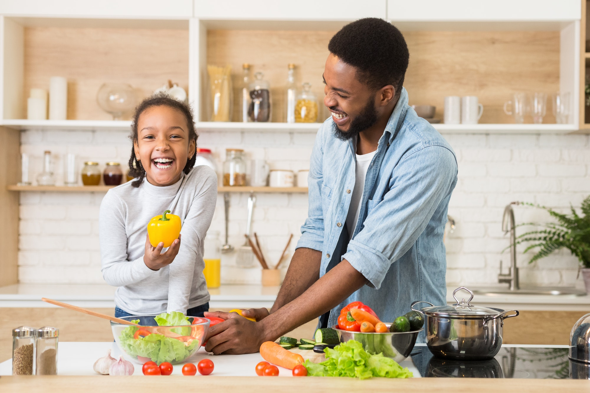 Cheerful afro girl holding pepper while helping father cooking dinner