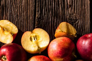 Background of apples whole and cut on wood